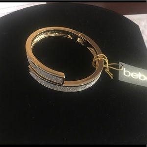 Bebe hinged, overlapping sparkly gold bracelet